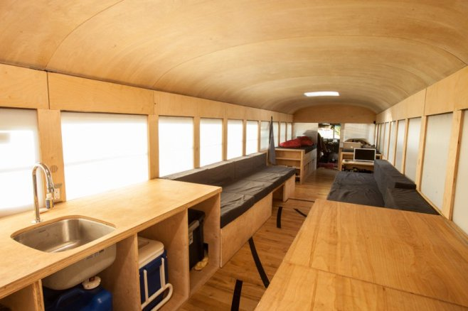 While most bus conversions cover up the existing windows to make the most of the space, architecture student Hank Butitta took a different approach, leaving them open while installing multi-purpose, transforming built-ins for a bright and highly functional interior.